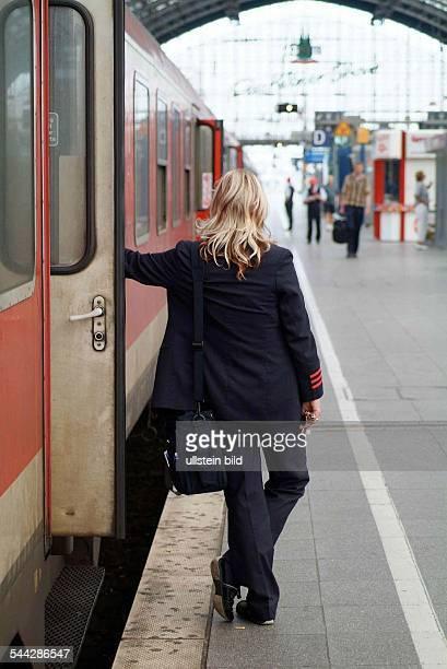 Deutschland NordrheinWestfalen Hauptbahnhof Köln Zugbegleiterin an der Zugtür auf dem Bahnsteig an einem Regionalzug der Deutschen Bahn