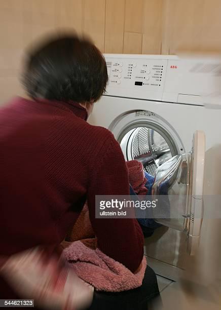 Deutschland Symbol Hausarbeit Hausfrau Putzen Putzfrau illegale Putzhilfe Frau gibt Waesche in eine Waschmaschine