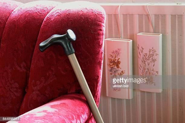 Deutschland Wohnungseinrichtung Einrichtung der Wohnung einer Seniorin Gehstock lehnt an einem roten Polstersessel Luftbefeuchter aus Keramik an der...