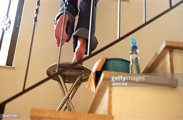 DeutschlandUnfallgefahren im Haushalt Sturzgefahr beim Putzen im Treppenhaus durch unsicheren Stand auf einem wackeligen Stuhl