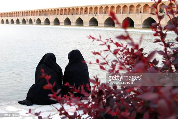 Deux adolescentes voilées de noir regardent la rivière Zâyandeh, à Ispahan, Iran, face au pont Si-o-se Pol , en avril 2015.
