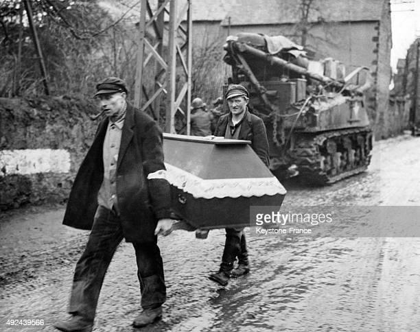 Deux Allemands transportent le cercueil d'une victime des bombardements alors que les tanks americains envahissent cette petite ville pres de...