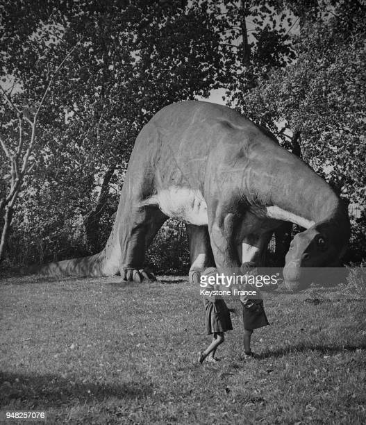 Deux enfants devant une maquette de dinosaure dans un parc d'Hambourg Allemagne en 1934
