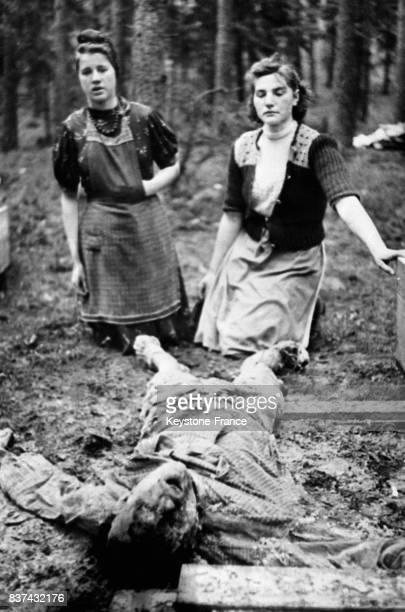 Deux femmes allemandes devant un cadavre torturé dans un camp de concentration en Allemagne en 1945