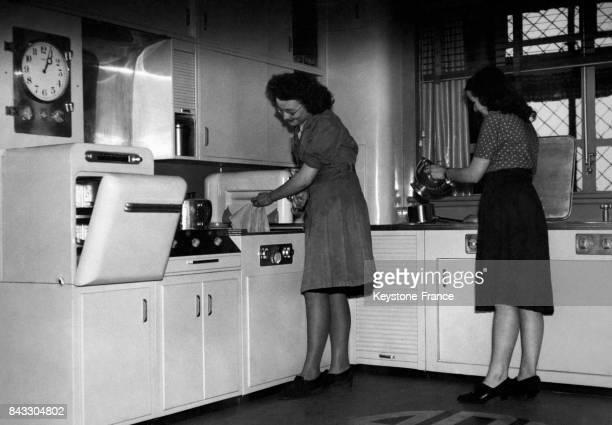 Deux femmes au travail dans une cuisine moderne en aluminium avec machine à laver à Londres RoyaumeUni en janvier 1946