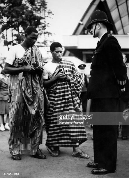 Deux footballeurs de l'équipe africaine Gold Coast qui joue pieds nus prennent en photo un policier britannique lors de leur visite touristique de la...