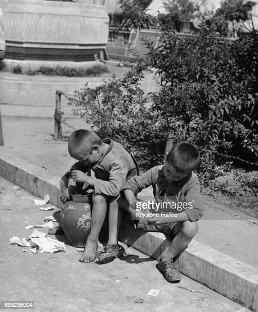 Deux garçons sales et pauvres assis sur le trottoir essaient de vendre la jarre à Athènes Grèce en 1947