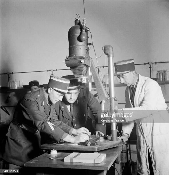 Deux gendarmes élèves des cours de photographie du fort de Châtillon France s'initient aux travaux d'agrandissement le 13 octobre 1951