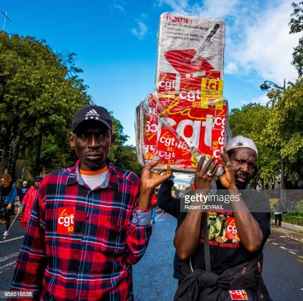 Deux hommes portent une pancarte représentant un couteau planté dans le code du travail lors de la manifestation contre les ordonnances modifiant ce...