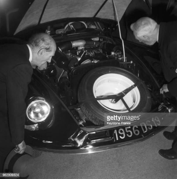 Deux hommes regardent de près le moteur de la Citroën DS19 la roue de secours et la prise d'air se trouvent de chaque côté de la plaque...