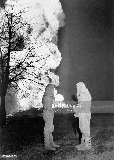 Deux hommes revetus de combinaisons d'amiante pres d'un puits de petrole en flammes suite a une explosion le 8 mars 1965 a Cortemaggiore Italie