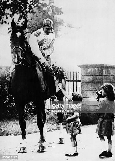 Deux jeunes Danoises présentent un bouquet de fleurs au roi Christian X qui comme chaque matin sort de sa résidence d'été faire une promenade à...