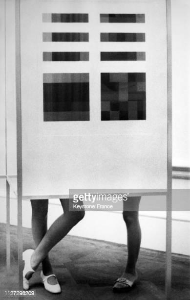 Deux jeunes femmes, mais seulement trois jambes, bizarrement, derrière un panneau dans une exposition sur le Bauhaus à la Royal Academy le 20...