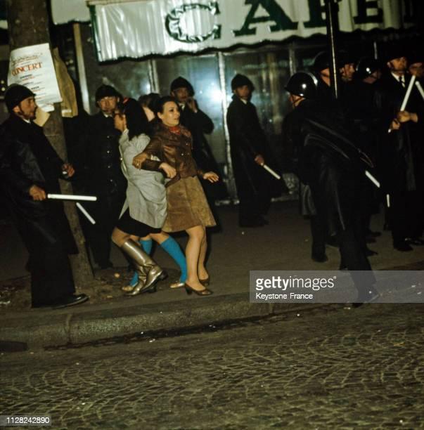 Deux jeunes femmes prises dans une charge de CRS place Saint-Germain, à Paris, France, le 23 mai 1968.