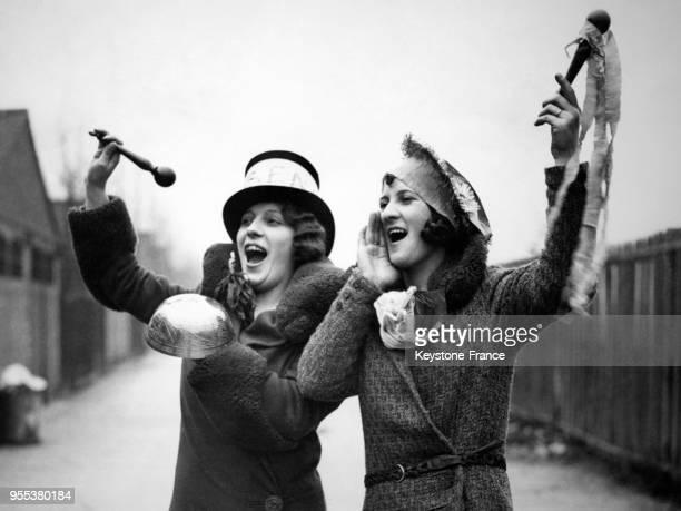 Deux jeunes femmes s'entraînent à crier leurs encouragements à leur équipe de football favorite Arsenal avant un match à Upton Park à Londres...