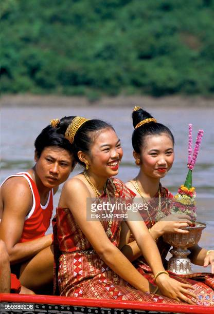 Deux jeunes filles dont une tient un trophée aux couleurs de son équipe durant la fête des pirogues circa 2000 en bordure du Mekong Laos