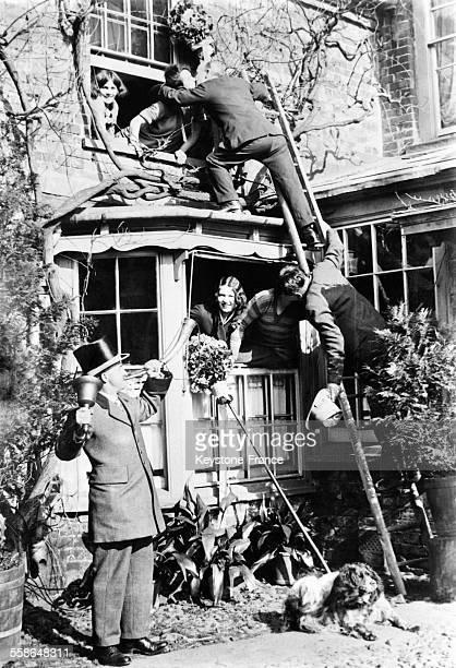 Deux jeunes gens escaladent une maison à l'aide d'une échelle pour embrasser la première femme qu'ils rencontrent à gauche le crieur du village...