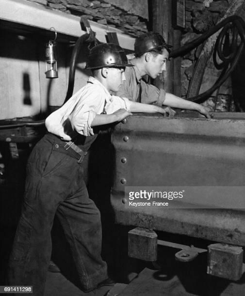 Deux jeunes mineurs en formation apprenant à pousser un chariot de charbon en 1954 à la mine de Bestwood dans le Nottinghamshire au RoyaumeUni