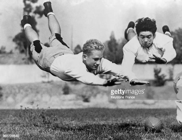 Deux joueurs de football américain exécutent un véritable plongeon sur le ballon aux EtatsUnis le 28 septembre 1934