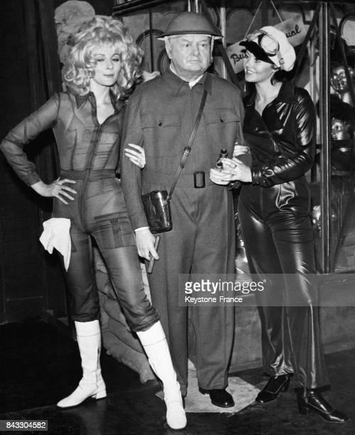 Deux modèles portant des combinaisons transparentes et en latex entourent un mannequin à l'effigie de Winston Churchill le 8 septembre 1969 au...