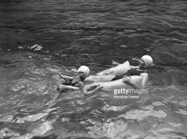 Deux nageurs font une démonstration d'un nouvel équipement mis au point par le professeur Chabel à la piscine ChamperretDanton le 30 mai 1934 à Paris...