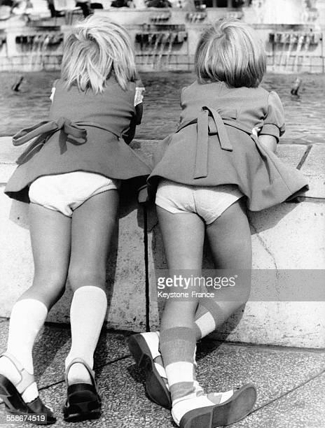 Deux petites filles vues de dos laissent voir leurs sousvêtements alors qu'elles observent les jeux d'eau d'une fontaine sur une place à Berlin...