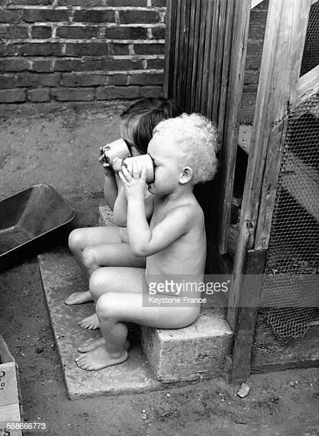 Deux petits enfants de la crèche de Hampstead ont enlevé leurs vêtements et boivent une tasse de lait assis sur une marche à Londres RoyaumeUni