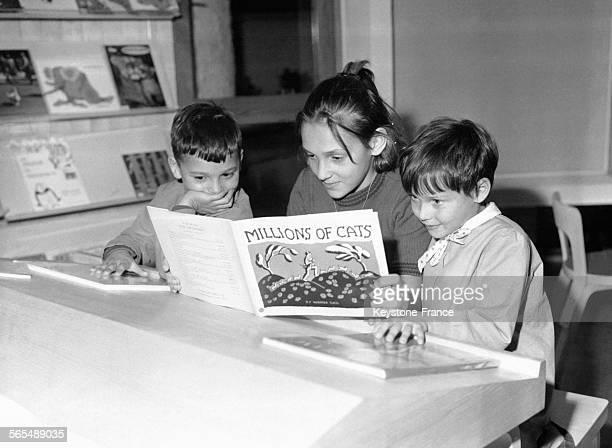 Deux petits garçons et une adolescente lisent un livre en anglais dans une salle de classe