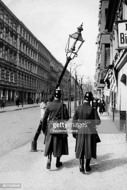 Deux soldats passent devant un réverbère cassé par les manifestations du 1er mai circa 1930 à Berlin Allemagne