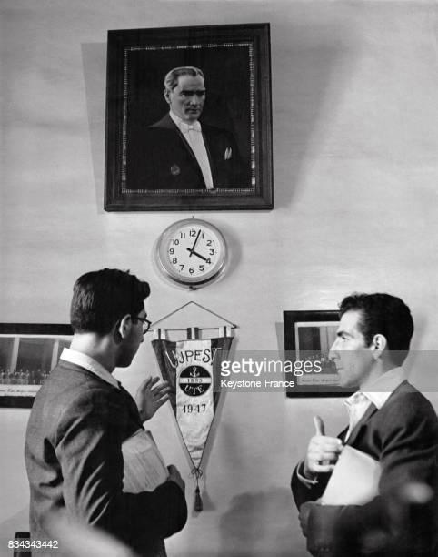 Deux étudiants de l'université de droit photographiés devant un portrait du Président turc regardent le fanion de l'équipe sportive de leur...