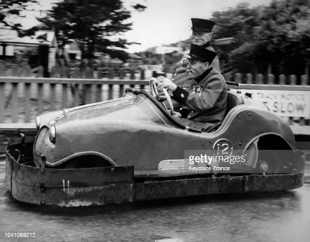 Deux vieillards s'amusent au volant d'une autotamponneuse le 14 juillet 1961 à Londres RoyaumeUni