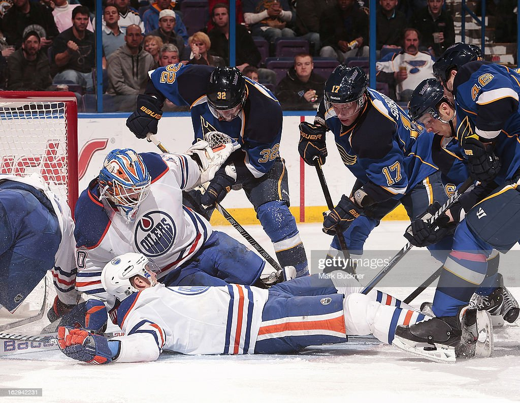 Devan Dubnyk #40 and Ladislav Smid #5 of the Edmonton Oilers cover the puck as Chris Porter #32, Vladimir Sobotka #17, Matt D'Agostini #36 and Roman Polak #46 of the St. Louis Blues try to poke it loose in an NHL game on March 1, 2013 at Scottrade Center in St. Louis, Missouri.