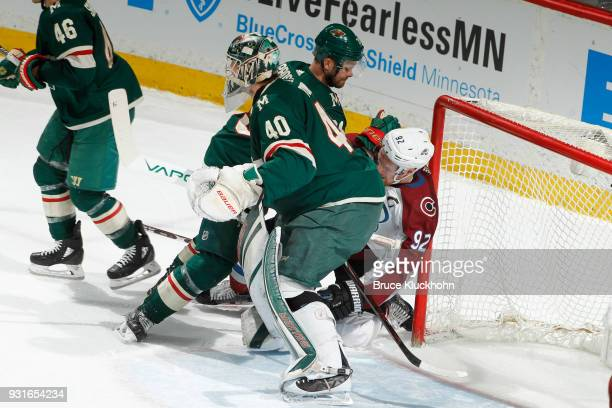 Devan Dubnyk defends his goal while his teammate Nate Prosser of the Minnesota Wild checks Gabriel Landeskog of the Colorado Avalanche during the...