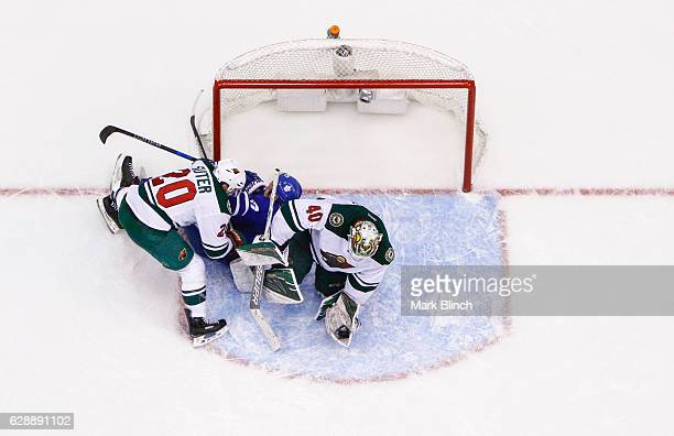Devan Dubnyk holds the puck as Ryan Suter of the Minnesota Wild collides with Leo Komarov of the Toronto Maple Leafs during the third period at the...