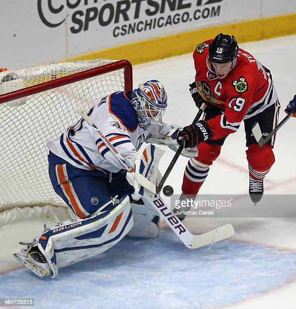 Devan Dubnyk of the Edmonton Oilers makes a save against Jonathan Toews of the Chicago Blackhawks at the United Center on January 12 2014 in Chicago...