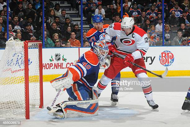 Devan Dubnyk of the Edmonton Oilers makes a save as Eric Staal of the Carolina Hurricanes skates in front of the net on December 10, 2013 at Rexall...