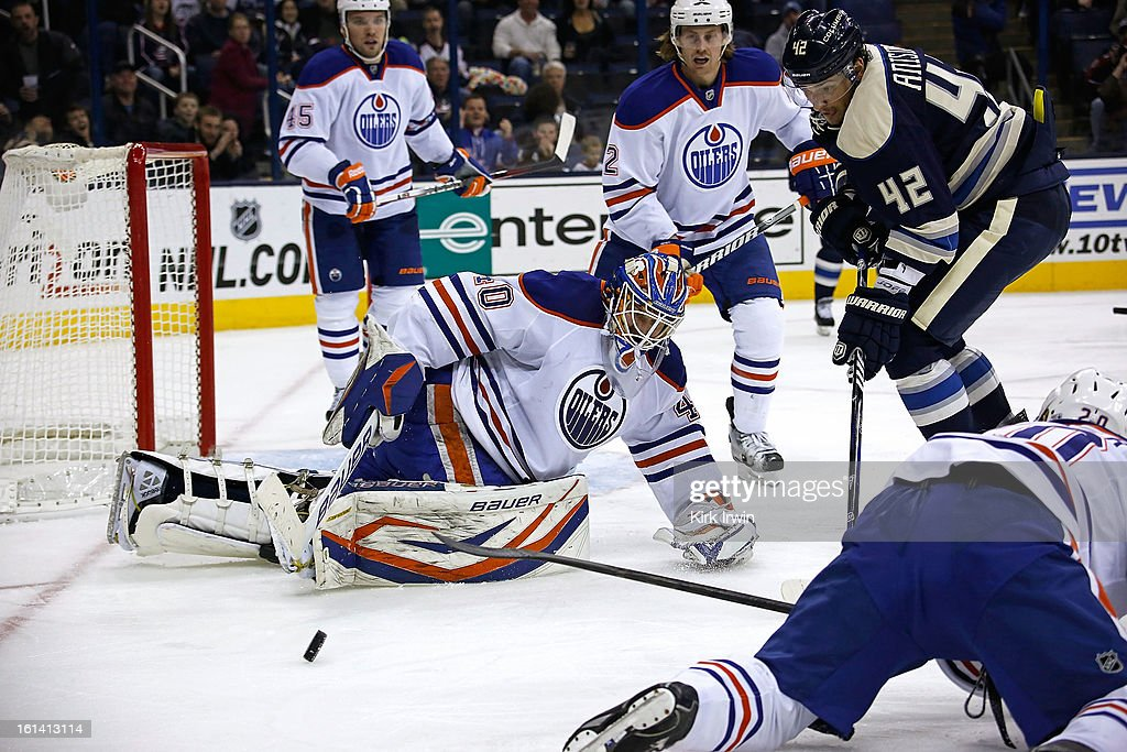 Devan Dubnyk #40 of the Edmonton Oilers reaches to knock away a rebound before Artem Ansimov #42 of the Columbus Blue Jackets is able to control the puck during the second period on February 10, 2013 at Nationwide Arena in Columbus, Ohio. Dubnyk stopped 39 shots as Edmonton defeated Columbus 3-1.