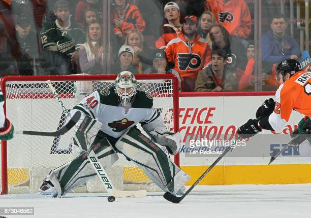Devan Dubnyk of the Minnesota Wild keeps his eyes on the puck while Michael Raffl of the Philadelphia Flyers reaches for the puck on November 11 2017...