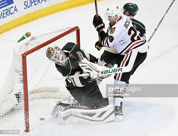 Devan Dubnyk of the Minnesota Wild looks on along with Bryan Bickell of the Chicago Blackhawks and Ryan Suter of the Minnesota Wild as the shot by...