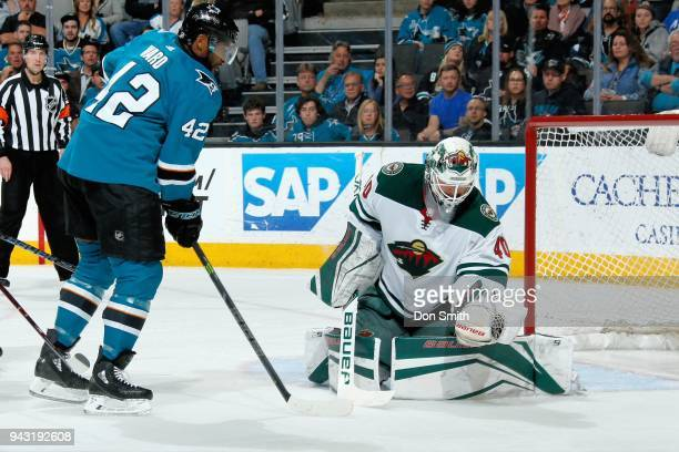 Devan Dubnyk of the Minnesota Wild makes a glove save as Joel Ward of the San Jose Sharks looks for the rebound at SAP Center on April 7 2018 in San...