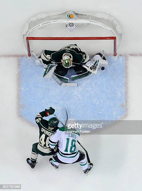 Devan Dubnyk of the Minnesota Wild makes a save in net as Jared Spurgeon of the Minnesota Wild and Patrick Eaves of the Dallas Stars look on during...