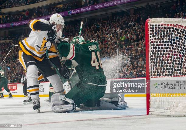 Devan Dubnyk of the Minnesota Wild makes a save on a charging Evgeni Malkin of the Pittsburgh Penguins during a game at Xcel Energy Center on...