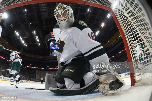 Devan Dubnyk of the Minnesota Wild picks up the puck after giving up a goal to the St Louis Blues in Game Three of the Western Conference First Round...