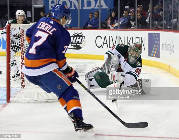 Devan Dubnyk of the Minnesota Wild shoots the puck away from the onrushing Jordan Eberle of the New York Islanders during the second period at the...
