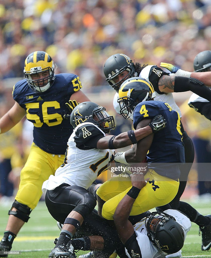 Devan Stringer #11 of Appalachin State makes the tackle on running back DeVeon Smith #4 of the University of Michigan during the second half of the game at Michigan Stadium on August 30, 2014 in Ann Arbor, Michigan. The Wolverines defeated the Mountaineers 52-14.