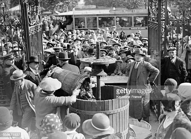 Devant le pressoir ont lieu le tirage et la dégustation du nouveau vin à Argenteuil France le 28 septembre 1931