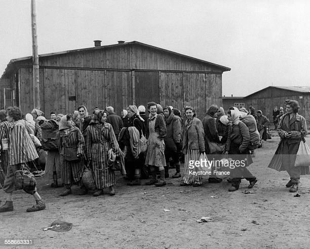 Devant les baraquements en bois des prisonnières politiques en tenues rayées et foulards sur la tête emportent quelques affaires à la sortie du camp...