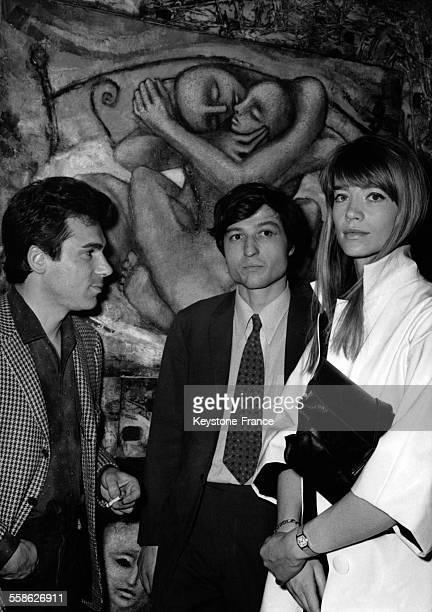 Devant une de ses toiles intitulée La Vie le peintre Jean Moulin entouré de Claude Nougaro et de Françoise Hardy lors du vernissage à la galerie...