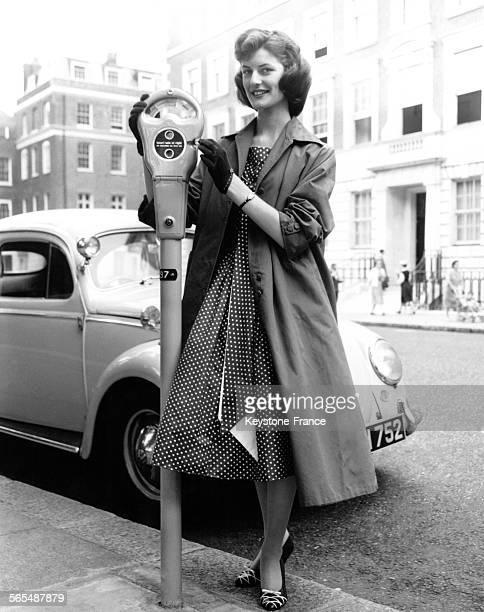 Devant une Volkswagen Coccinelle Lorraine Buist mettant une pièce de monnaie dans le parcmètre à Mayfair Londres RoyaumeUni le 10 juillet 1958