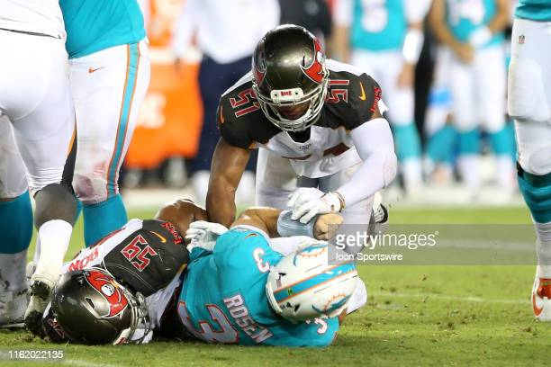 Devante Bond and Kevin Minter of the Bucs combine to bring down Dolphins quarterback Josh Rosen during the preseason game between the Miami Dolphins...
